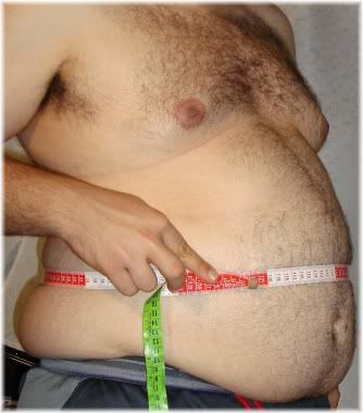 man measuring fat belly waist