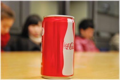 can of coke with kids in background