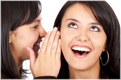 girl whispering into girl's ear