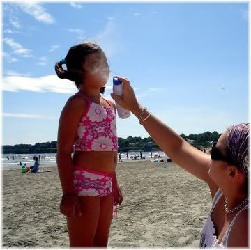 mother applying sunscreen to daughter