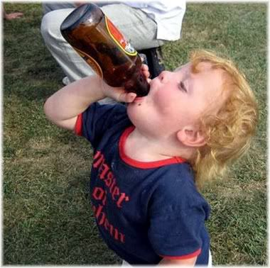 young boy with beer bottle in mouth