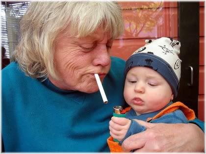 grandma with cigarette in mouth next to baby holding lighter