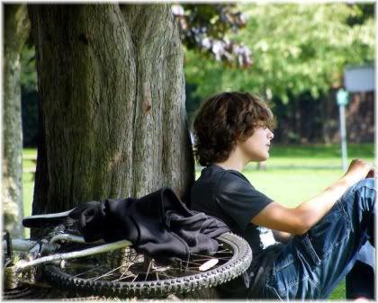 boy sitting by tree