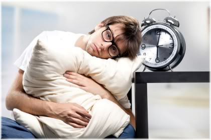 man holding pillow next to alarm clock