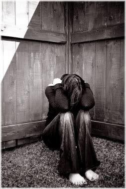 woman in corner on floor crying