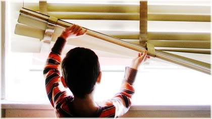 boy lifting up blinds looking out window