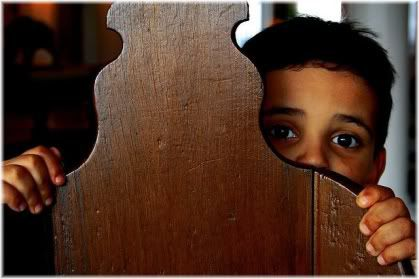 boy hiding behind chair