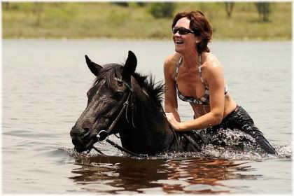 woman riding horse in water